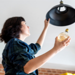 woman putting in a light bulb